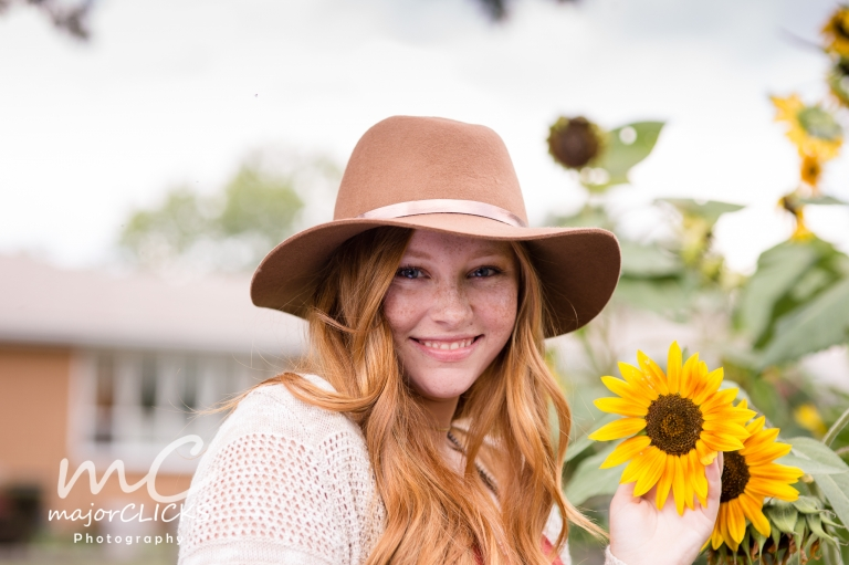 Senior girl with brown hat in sunflower field
