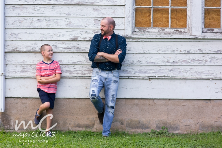 Father and son leaning against a barn wall