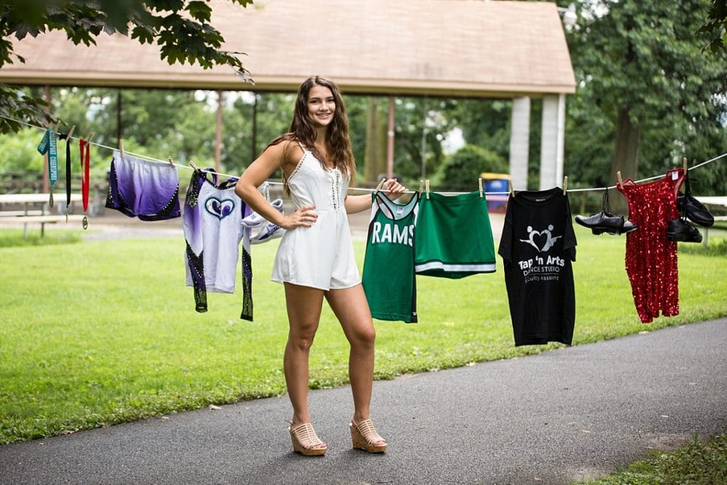 Senior girl in park posing with dance and cheer uniforms on clothes line