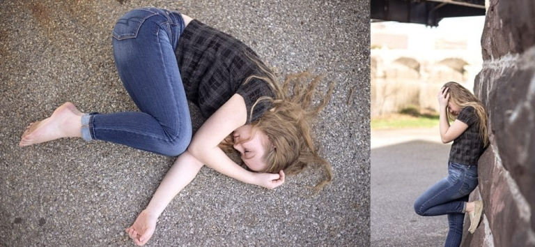 Long blond hair girl in jeans curled up on the ground