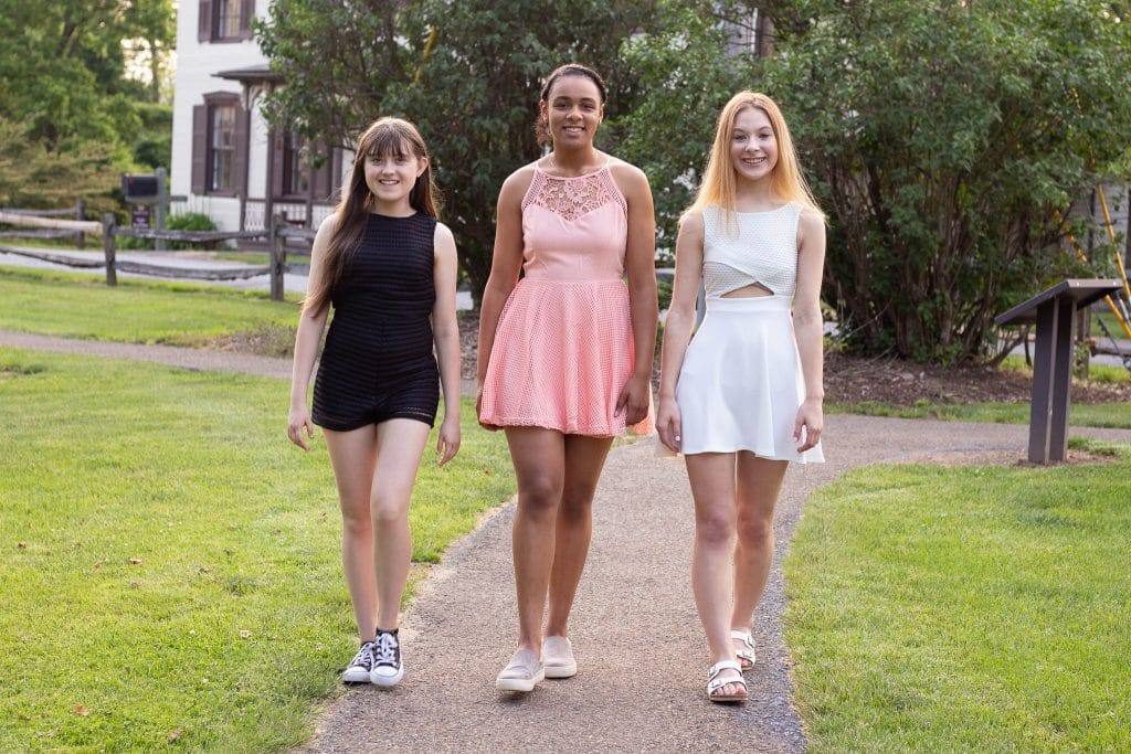 Three senior girls in homecoming dresses walking down a path
