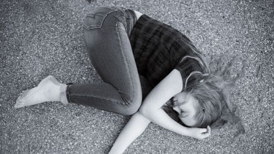 Black & white image of depressed girl curled up in fetal position on the street