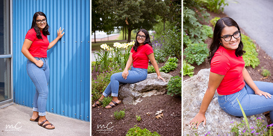 Senior Pics of a brunette girl in jeans and red shirt against a blue wall