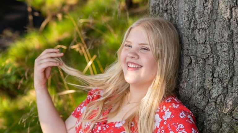 Red Land High School Senior in red top with blond hair leaning against a tree